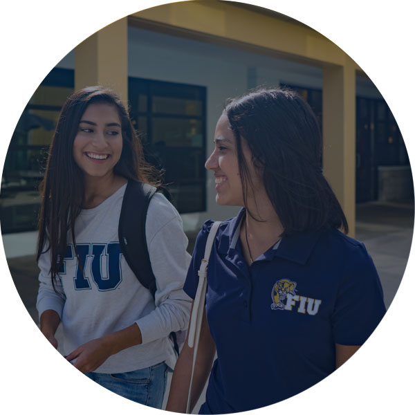 photo of two female students smiling at each other